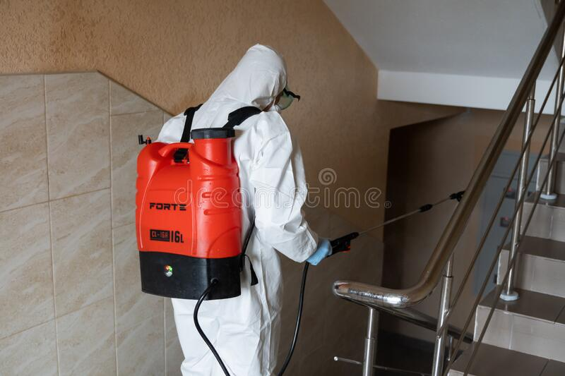 UKRAINE, KYIV - May 20, 2020: Man in a white protective suit and mask is sanitizing interior surfaces inside buildings. While the coronavirus epidemic for stock photo