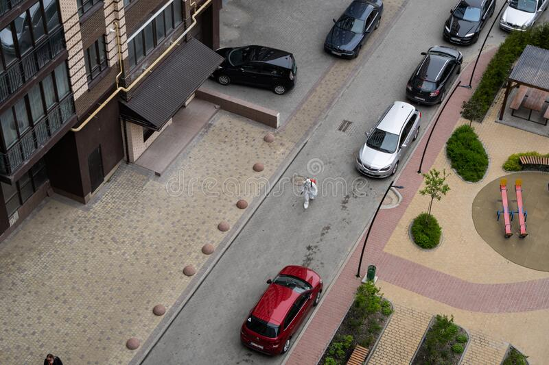 UKRAINE, KYIV - May 20, 2020: Man in a white protective suit and mask is walking on a street for sanitizing interior. Surfaces inside buildings while the royalty free stock photography