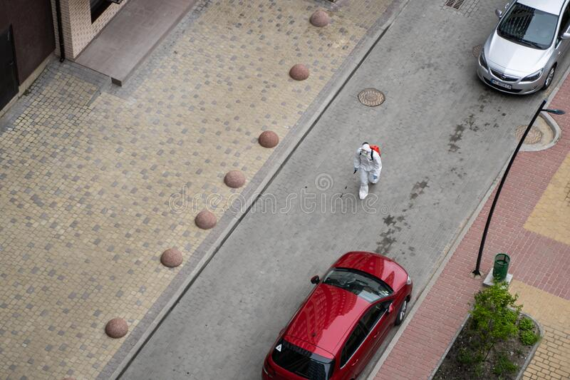 UKRAINE, KYIV - May 20, 2020: Man in a white protective suit and mask is walking on a street for sanitizing interior. Surfaces inside buildings while the royalty free stock photos