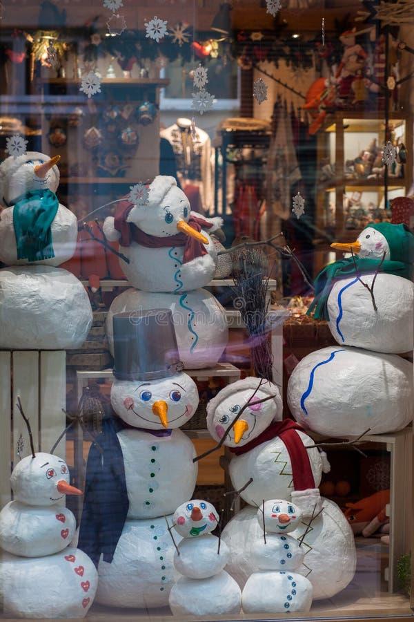 Ukraine, Lemberg - 6. Dezember 2018 Glückliche Schneemänner in den bunten Hüten, mit Schals ein Schaukastenspeicher stockfotografie