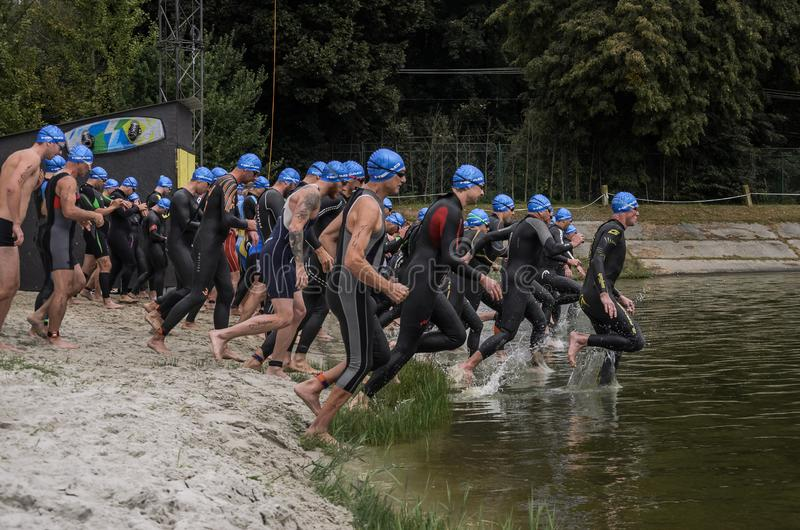 UKRAINE, LVIV - SEPTEMBER 2018: Athletes in wetsuits at the start run into the water for a swim in the triathlon competition. Athletes in wetsuits at the start royalty free stock image