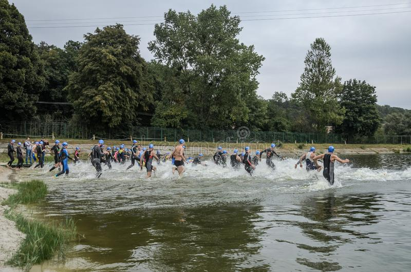 UKRAINE, LVIV - SEPTEMBER 2018: Athletes in wetsuits at the start run into the water for a swim in the triathlon competition. Athletes in wetsuits at the start royalty free stock photo
