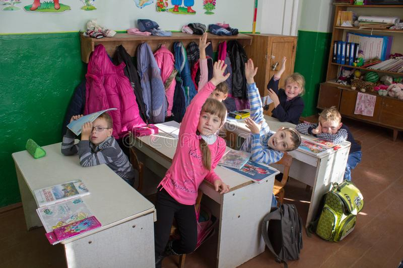 Kids at the lesson,3.11. 2014 Ukraine Mervichi a primary school student at a lesson raised his hands to answer stock photography
