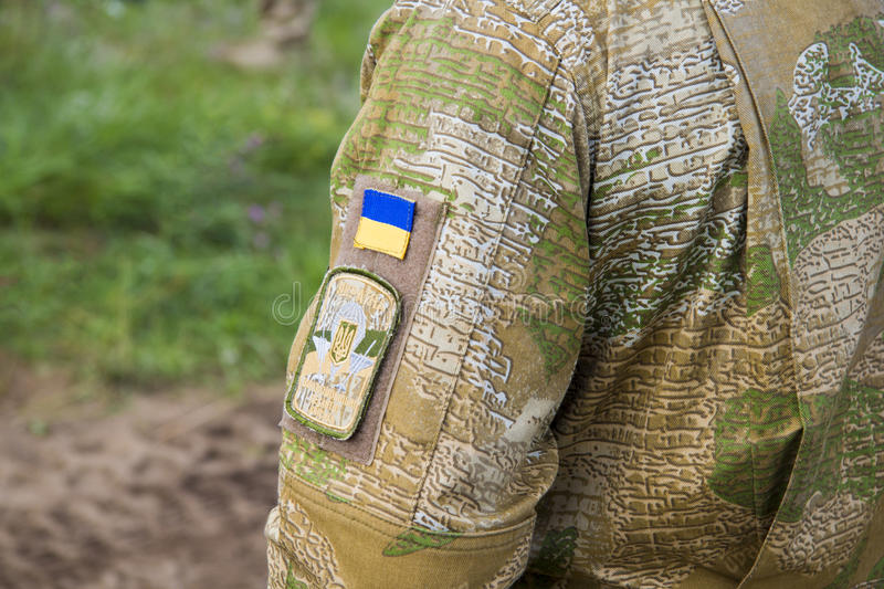 Ukraine national flag with an army patch on a military field jacket stock images