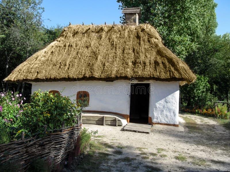 Ukraine, Pyrohiv Kiew - 17. September 2017: Kleines ukrainisches traditionelles Haus mit einem Blumengarten - Vorderansicht lizenzfreie stockfotografie