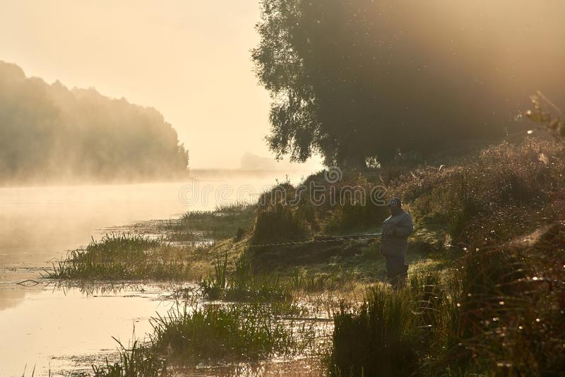 Ukraine, River Desna -September 7, 2019: A man fishes on the river bank on an early foggy morning stock image