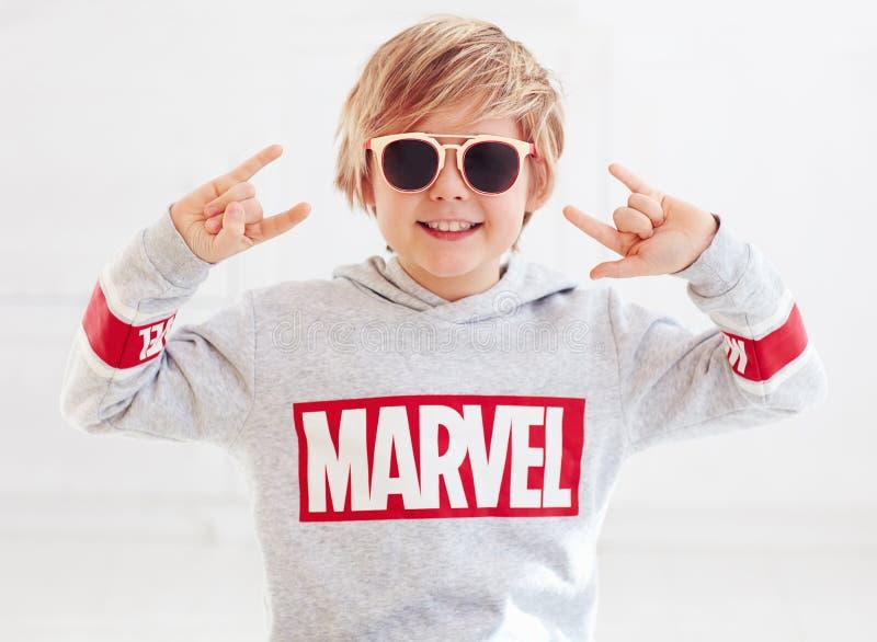 Ukraine- September 30, 2018: Portrait of blonde smiling boy with rock finger sign anf marvel logo on sweater. Ukraine - September 30, 2018: Portrait of blonde stock photos