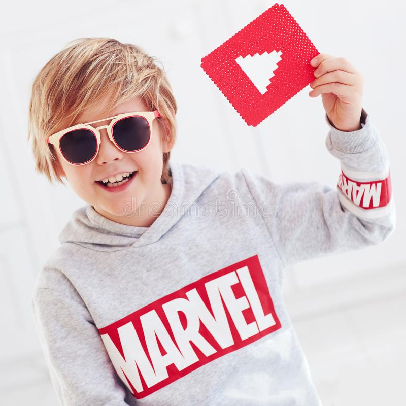 Ukraine- September 30, 2018: Portrait of cute happy boy, kid with marvel logo and youtube play icon stock photography