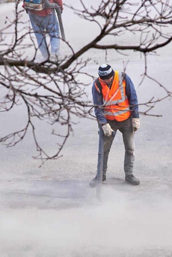 Ukraine,Shostka, Mira street -March 26, 2019: Workers repair asphalt road royalty free stock image