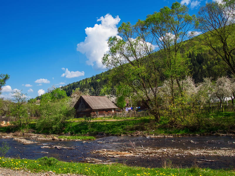 Ukraine, wooden house on the bank of the superficial mountain ri. Ver in the Carpathians. Spring in mountains, the small, not deep river and the small village stock image
