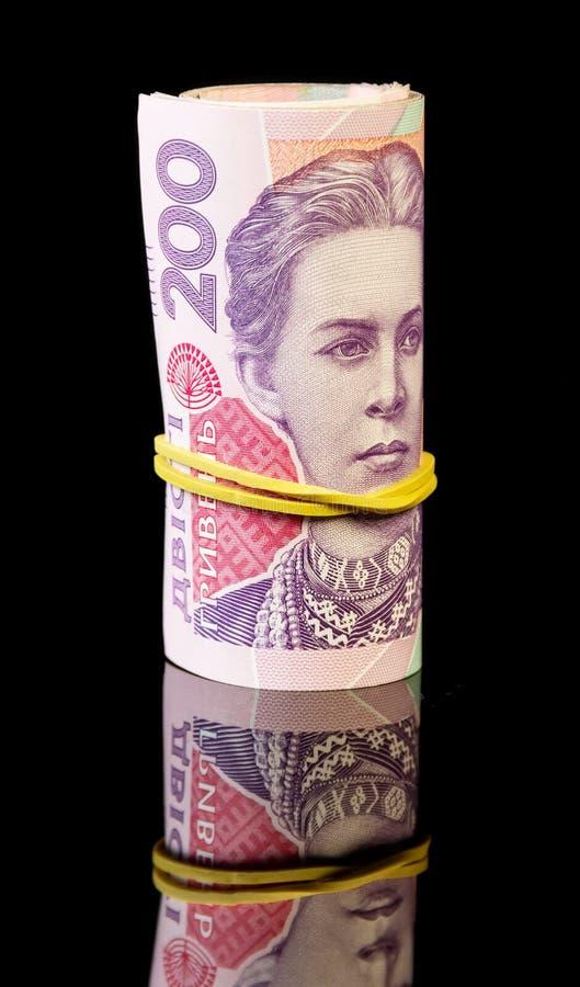 Ukrainer gerolltes Geld auf Schwarzem lizenzfreie stockbilder