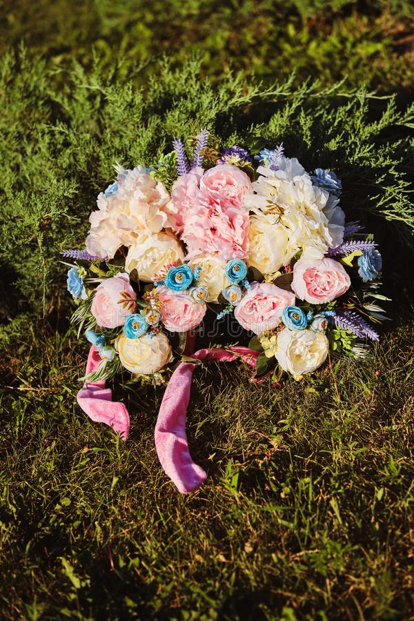 Ukrainian authentic national wreath of flowers laying on a green grass. Close-up. Ukrainian authentic national wreath of colorful flowers is laying on a green royalty free stock image