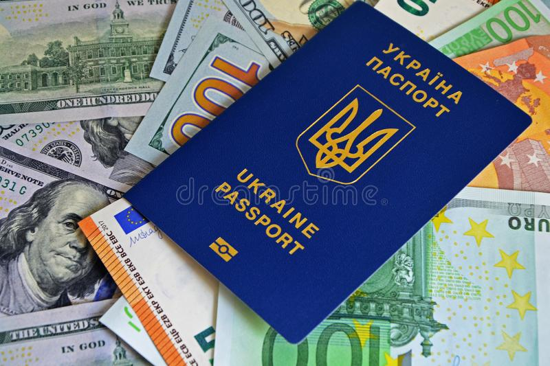 The Ukrainian biometric passport is on paper euro bills and dollars. Concept: increase of salaries, Ukrainians go abroad to work royalty free stock image