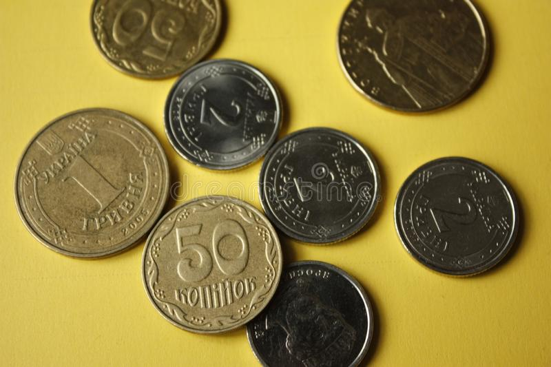Ukrainian coins isolated on yellow background. Close-up Coins are located in the center of the frame. Conceptual image. 1.2 hryvnia 50 kopecks stock photography