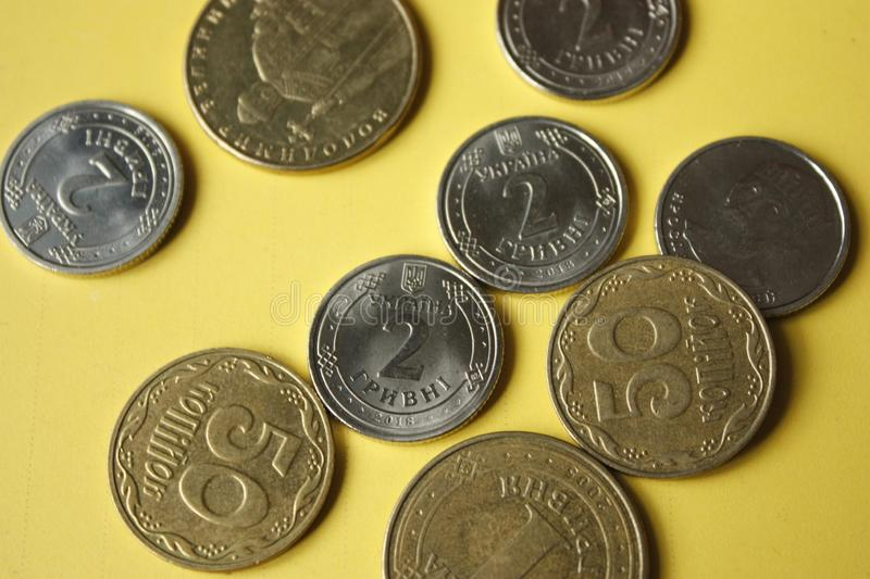 Ukrainian coins isolated on yellow background. Close-up Coins are located in the center of the frame. Conceptual image. 1.2 hryvnia 50 kopecks black euro one royalty free stock image