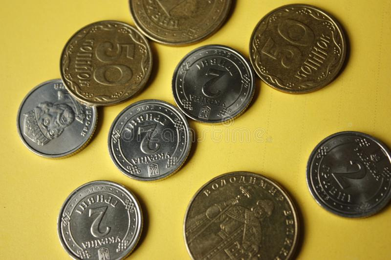 Ukrainian coins isolated on yellow background. Close-up Coins are located in the center of the frame. Conceptual image. 1.2 hryvnia 50 kopecks black euro one stock photo