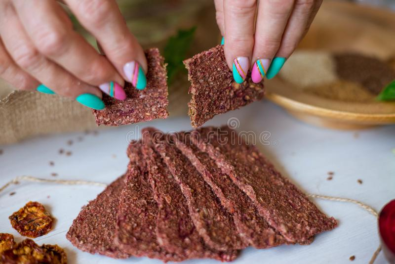 Ukrainian Crispbread  with beetroot and tomato in hands. Healthy diet food. Bread cakes on a white background in the ingredient. Seasoning stock photos