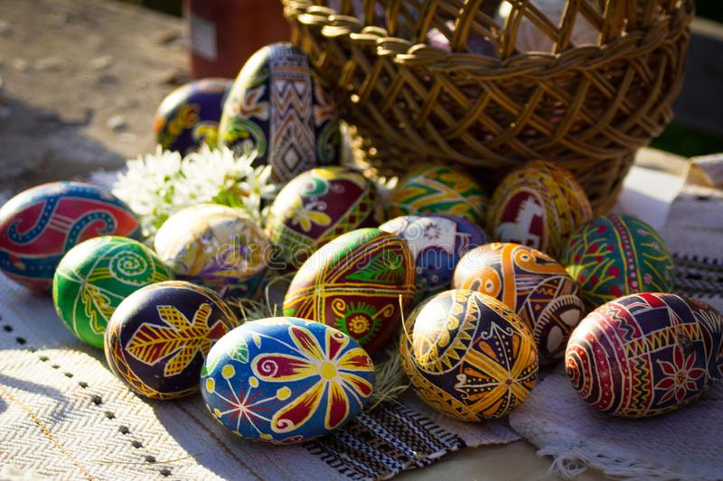 Ukrainian Easter eggs `pysanky` beside a basket. Horizontal close up image of ukrainian Easter eggs `pysanky`on the background of the basket and embroidered stock photo