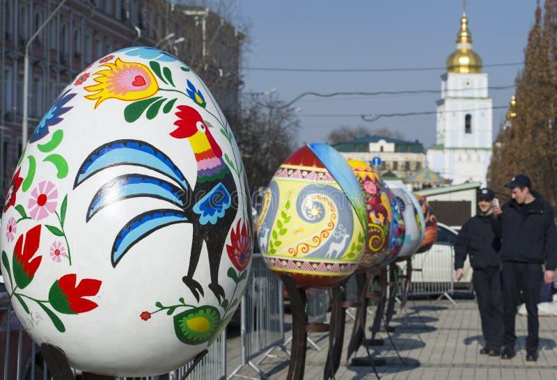 Ukrainian festival of Easter eggs. Kyiv / Ukraine - April 4, 2018: The Ukrainian pysanky festival. Two policemen take photo of the giant easter eggs stock photos