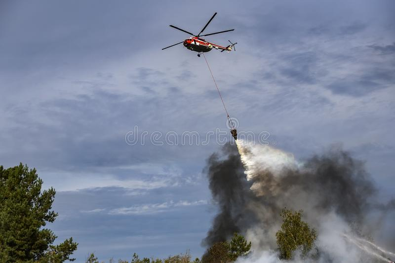 Ukrainian firefighting helicopter dropping a load of water to extinguish the fire in the forest stock images