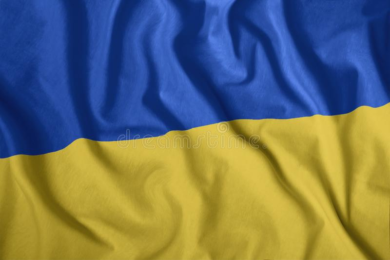 The Ukrainian flag is flying in the wind. Colorful, national flag of Ukraine. Patriotism, a patriotic symbol. Wrinkled cloth stock illustration