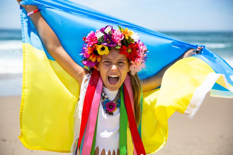 Ukrainian girl carries blue and yellow flag of Ukraine fluttering on the blue sky background royalty free stock photos