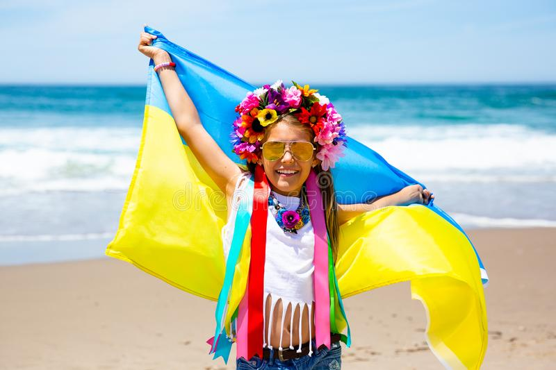 Little girl carries blue and yellow flag of Ukraine fluttering on the blue sky and sea background stock photos