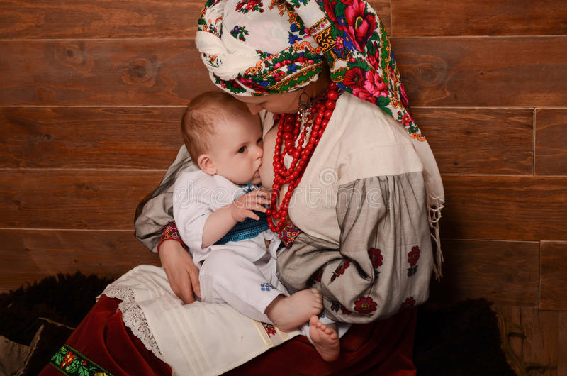 Ukrainian mother breastfeeding and hugging her baby. royalty free stock photography