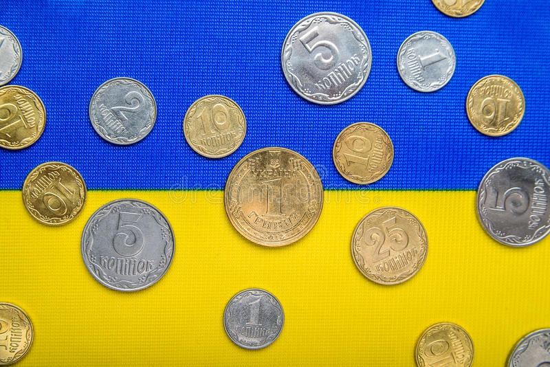 Ukrainian national coins against the background of the national yellow-blue flag. Eurovision currency. Ukrainian national coins against the background of the stock photos