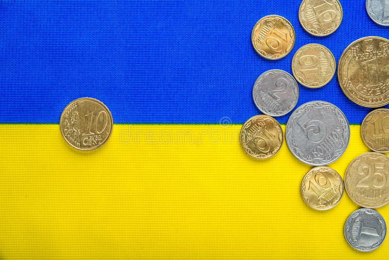 Ukrainian national coins and ten euro cents against the background of the national yellow-blue flag. Eurovision currency. Ukrainian national coins and ten euro stock photo