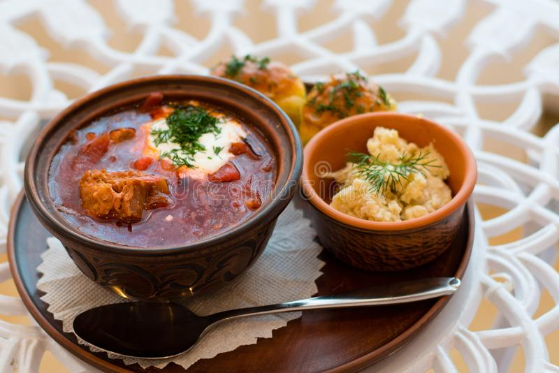 Ukrainian national cuisine, red borsch with meat and sour cream on a tray with lard and garlic dumplings royalty free stock photo