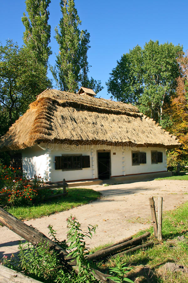 Ukrainian rural cottage with a straw roof. Ancient traditional ukrainian rural cottage with a straw roof at autumn season stock images