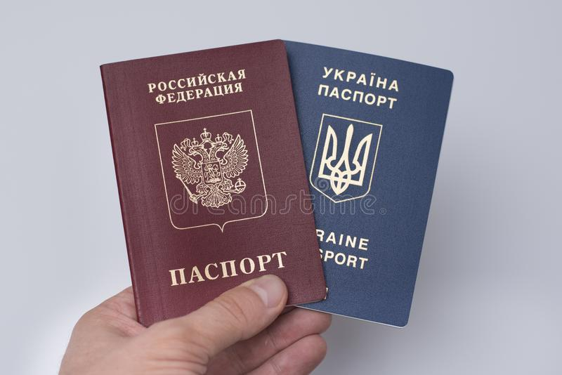 Ukrainian and Russian international passports in the man`s hand. royalty free stock photo