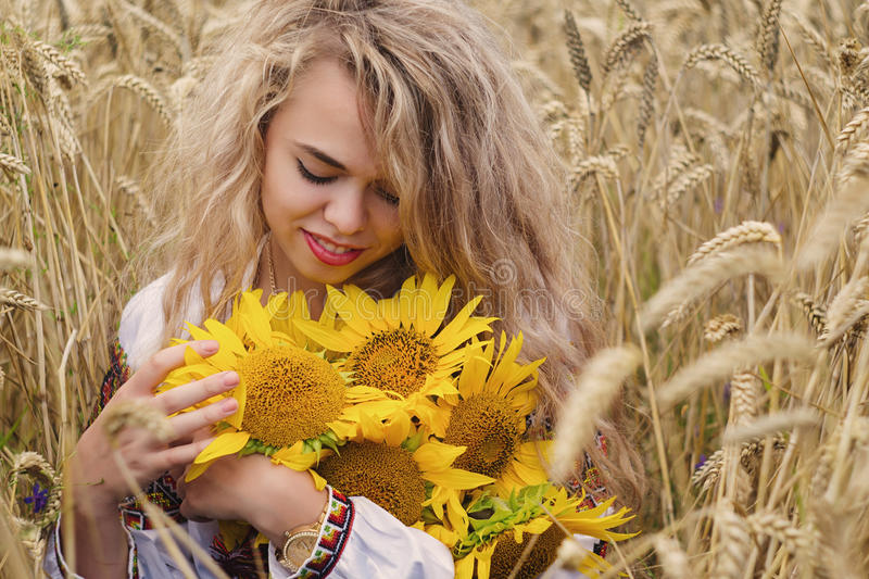 Ukrainian smelling sunflowers and standing among spikelets in field. stock photos