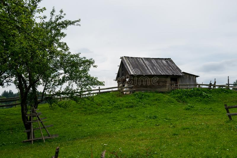 Wooden barn in village garden. Ukrainian village scene - a green garden on a hill and fenced modest log barn. Dilapidated structure in farm community near royalty free stock photography