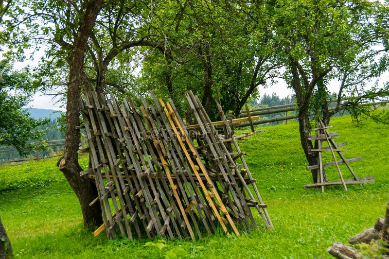 Wooden blanks for drying hay. Ukrainian village scene - old fenced green apple garden with wooden blanks for drying hay. Private property of ethnic Hutsuls in royalty free stock photography