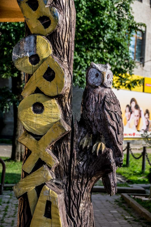 Wooden art - the Vorokhta inscription and owl figure. Ukrainian Wooden art - the Vorokhta inscription and owl figure close-up. Tree bark texture stock photo
