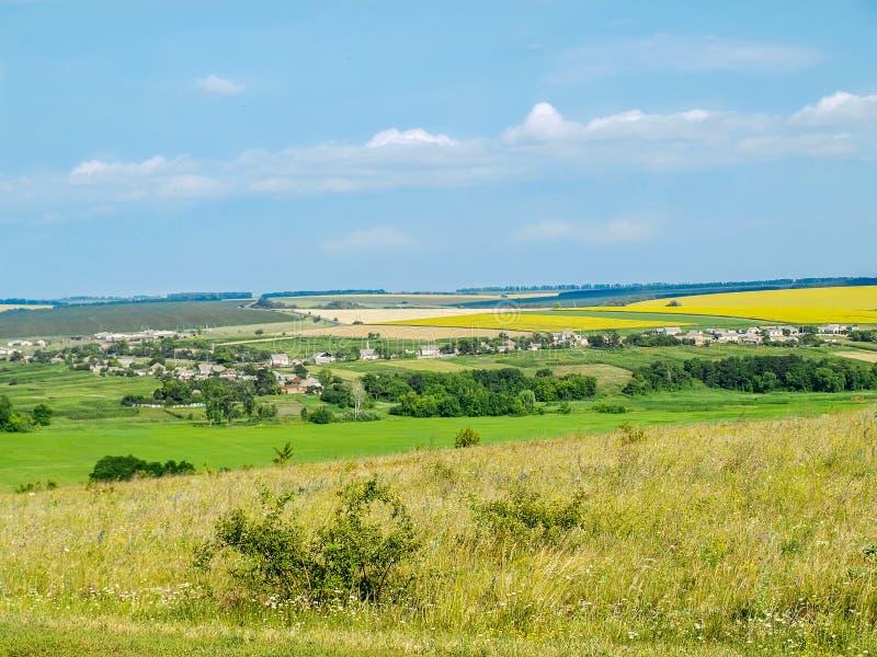 Ukrainische Landschaft - Dorf unter Feldern lizenzfreie stockbilder