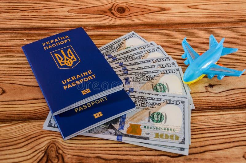 Ukrainische Pässe, Dollar und Spielzeugflugzeug auf einem hölzernen Hintergrund stockbild