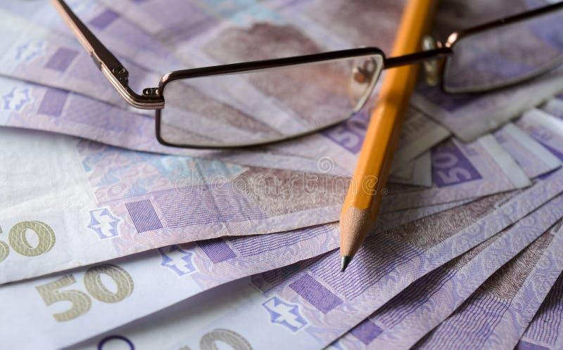 Ukrainisches hryvnia mit Bleistift und Gläsern Ukrainisches Geldfoto lizenzfreie stockbilder