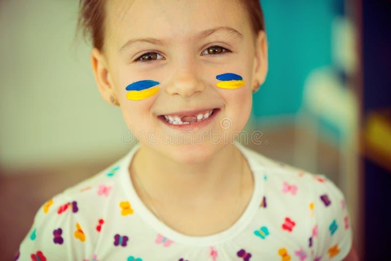 Ukrainisches Mädchen mit Staatsflagge auf Backe stockfotografie