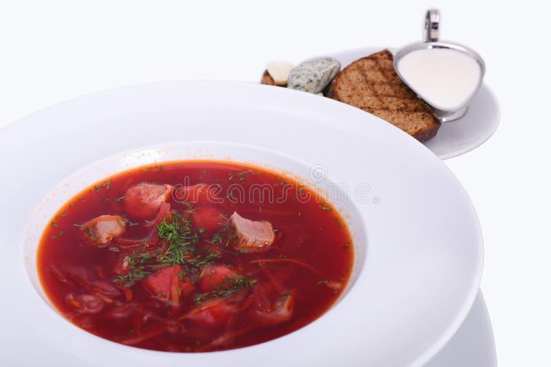 Ukrainsk borsch med gr?ddfil, br?d med sp?cker, den nationella matr?tten Foton?rbild p? den vita plattan fotografering för bildbyråer