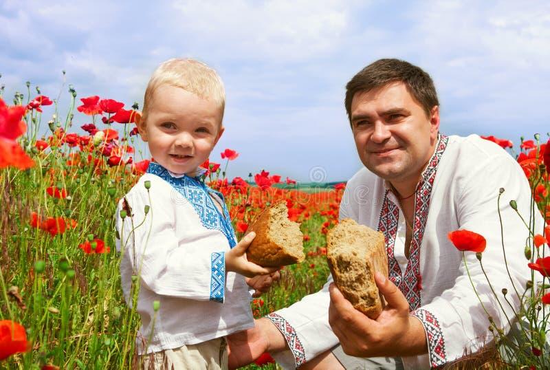 Ukrainsk familj i vallmofält royaltyfri fotografi