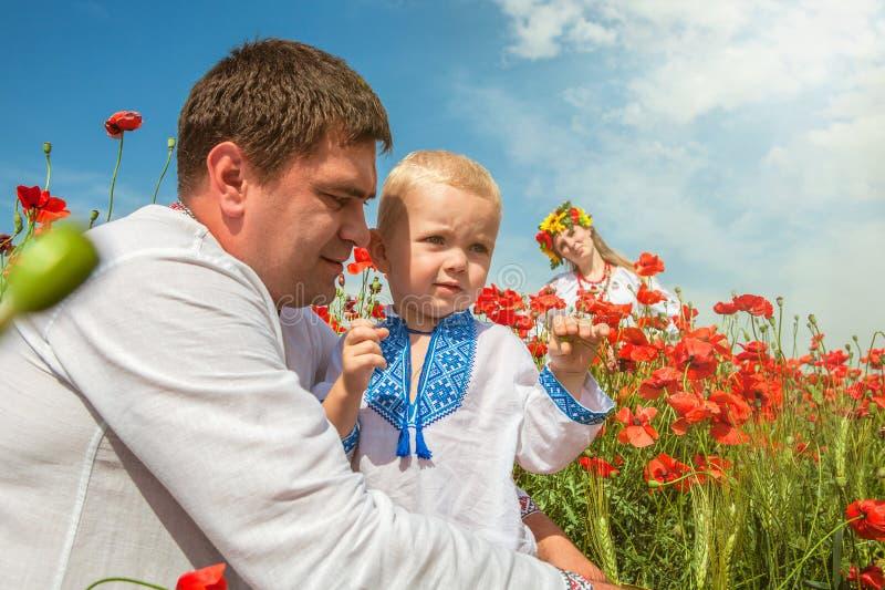 Ukrainsk familj med den lilla sonen på vallmofält royaltyfri bild