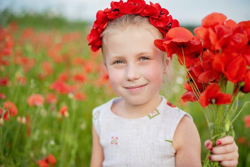 Ukrainsk härlig flicka i vyshivanka med kransen av blommor i ett fält av vallmo och vete utomhus- st?ende i vallmo flicka arkivbilder