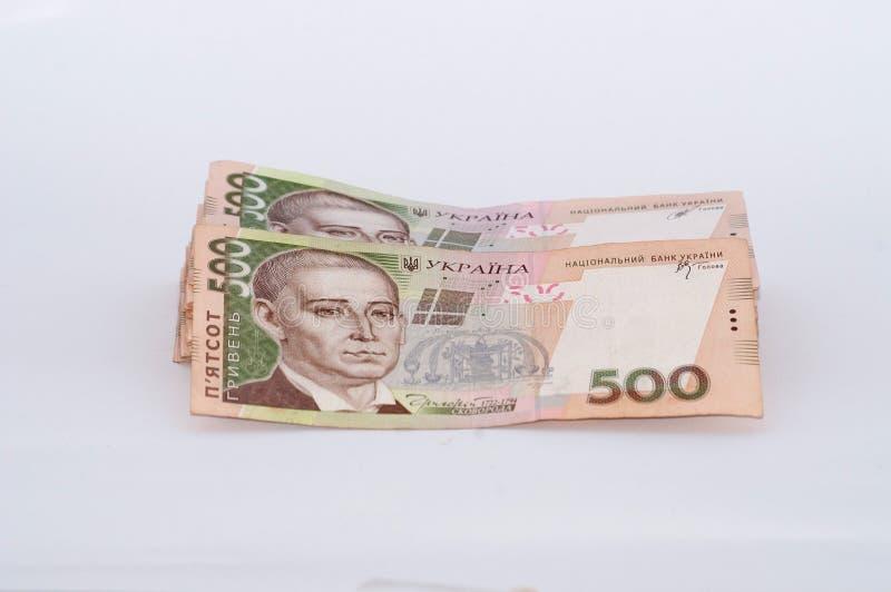 Ukrainsk hryvnia f?r pengar p? en vit bakgrund, en stor packe av r?kningar arkivbild