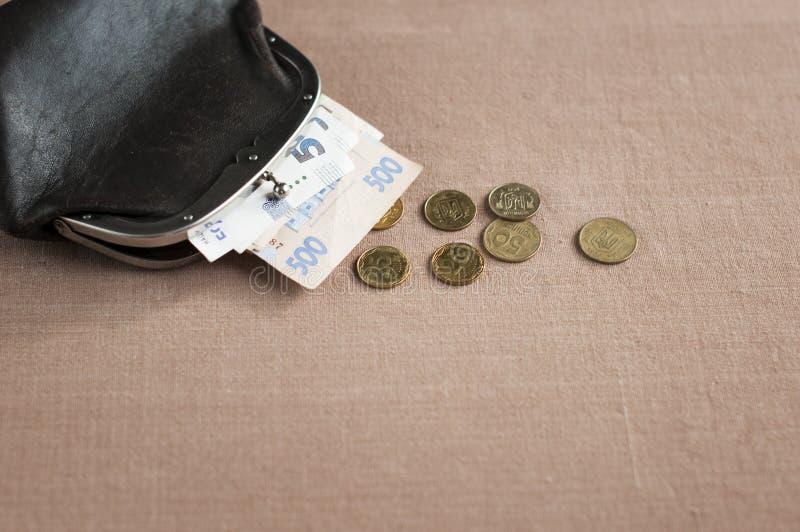 Ukrainsk hryvnia med encentmynt i en tappningbrunthandväska, royaltyfria foton