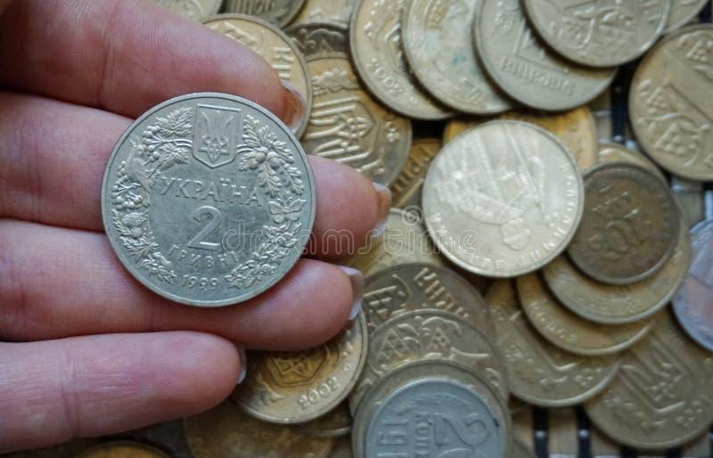 Ukrainska mynt i valörer av 1 hryvnia och andra, vek i en glidbana Eagle och svansar arkivbilder