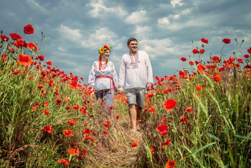 Ukrainska par går till och med vallmofält royaltyfria bilder
