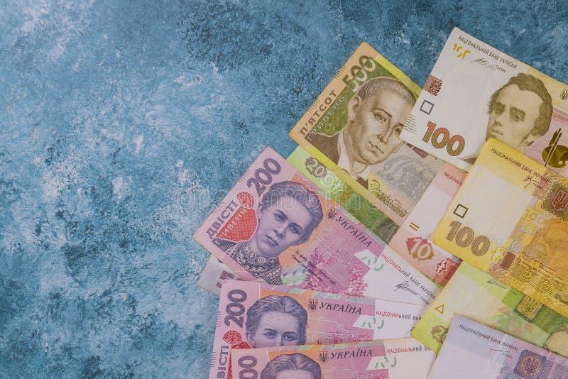 Ukrainska pengar på blå bakgrund bakgrundsbegreppet bantar guld- ?ggfinans royaltyfri bild